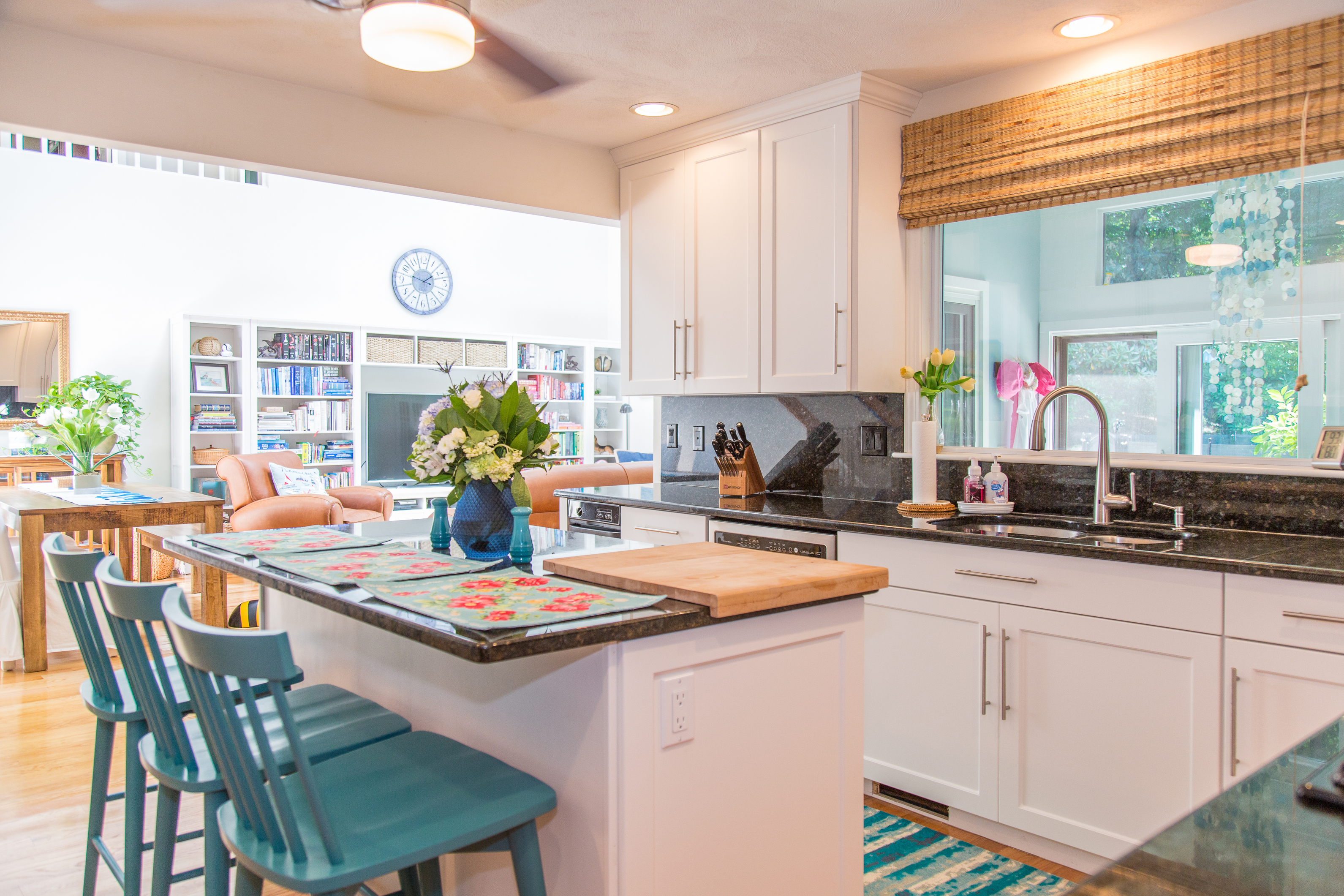 White Cabinetry with a black countertop and backsplash and light wood flooring