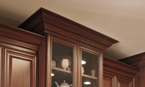 Dark Cherry Wood Glass-Front Kitchen Cabinet with Crown Molding