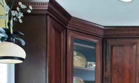 Dark Wood Glass-Front Kitchen Cabinet with Dentil Crown Molding