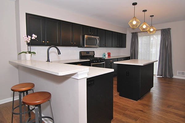 Kitchen with Black Cabinets and White Countertops
